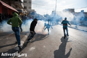 A Palestinian youth with a gas mask grabs a tear gas grenade fired by Israeli forces during clashes in the West Bank town of Bethlehem protesting Israeli attacks on Gaza, November 20, 2012. (photo: Ryan Rodrick Beiler/Activestills.org)